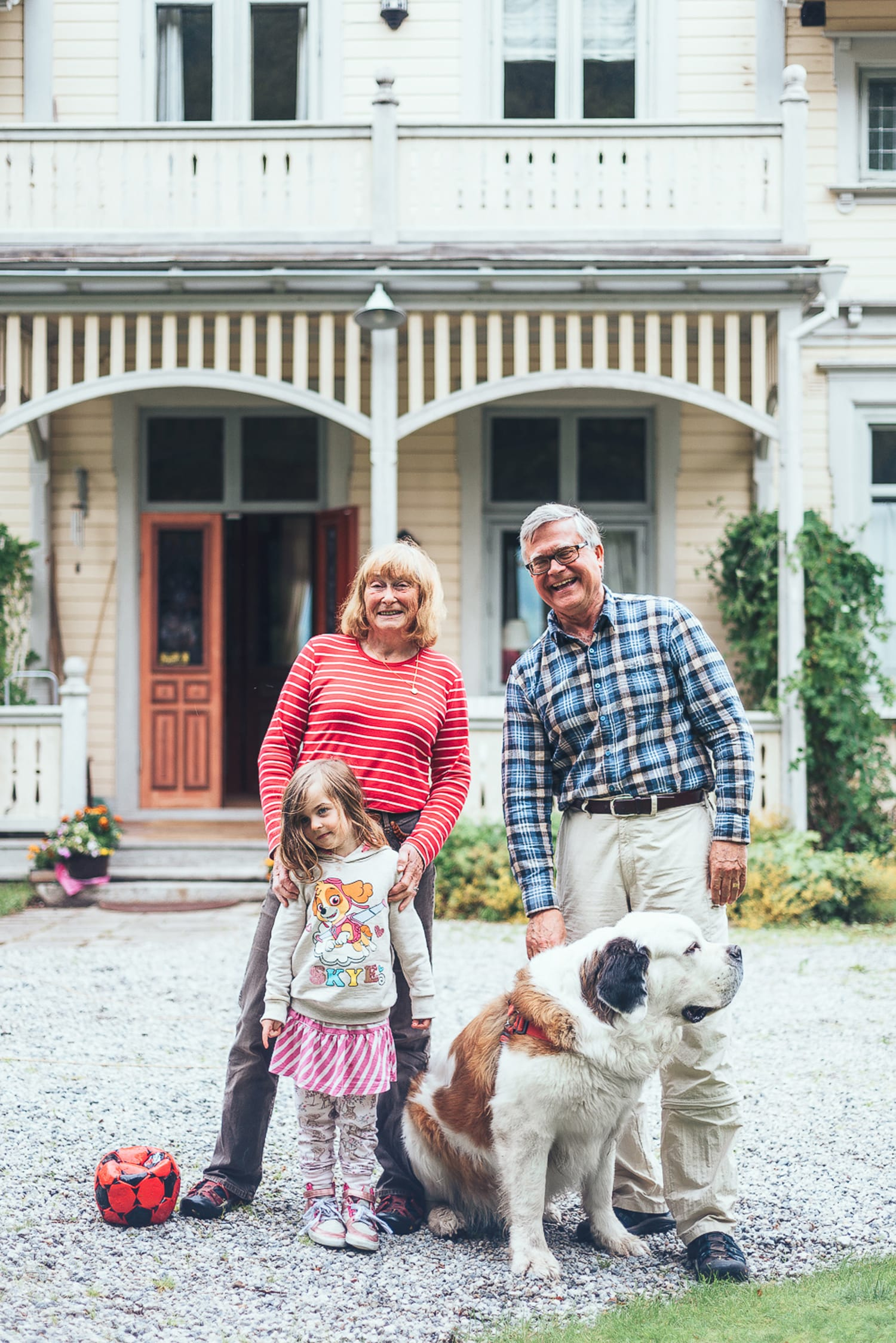 grandparents, grandchild and dog outside their house