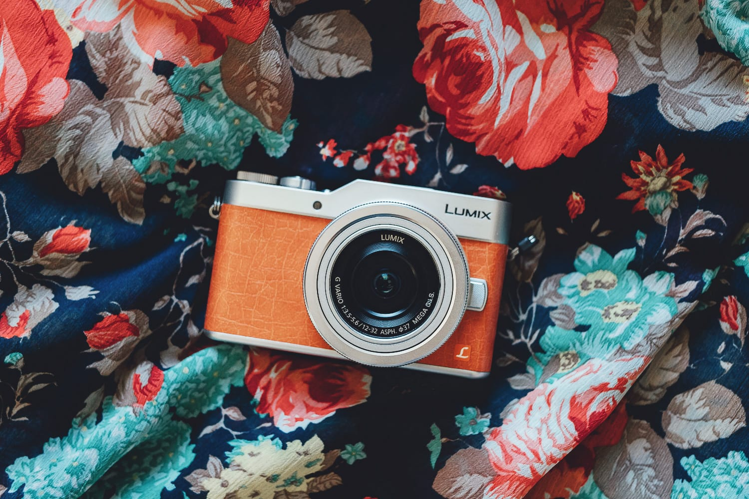 orange camera on a floral fabric