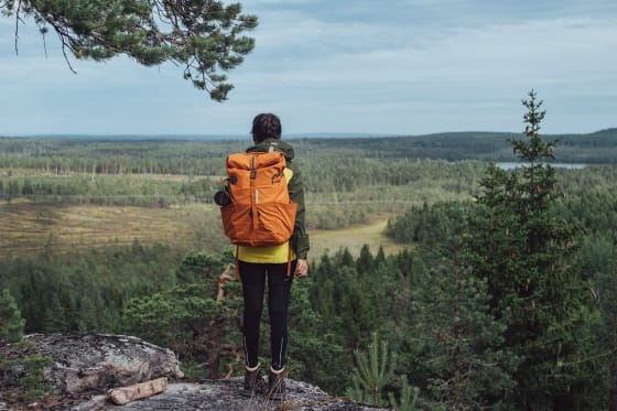 Girl with backpack on an outlook in a forest