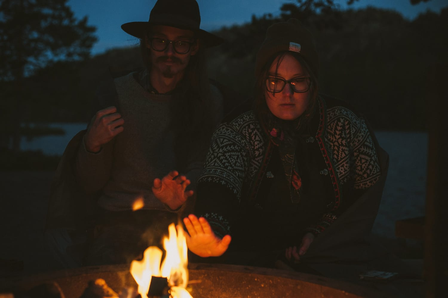 hikers getting warm by a fire at night