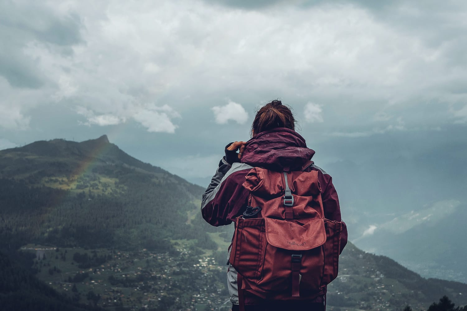 Woman with backpack standing on a mountain in the rain