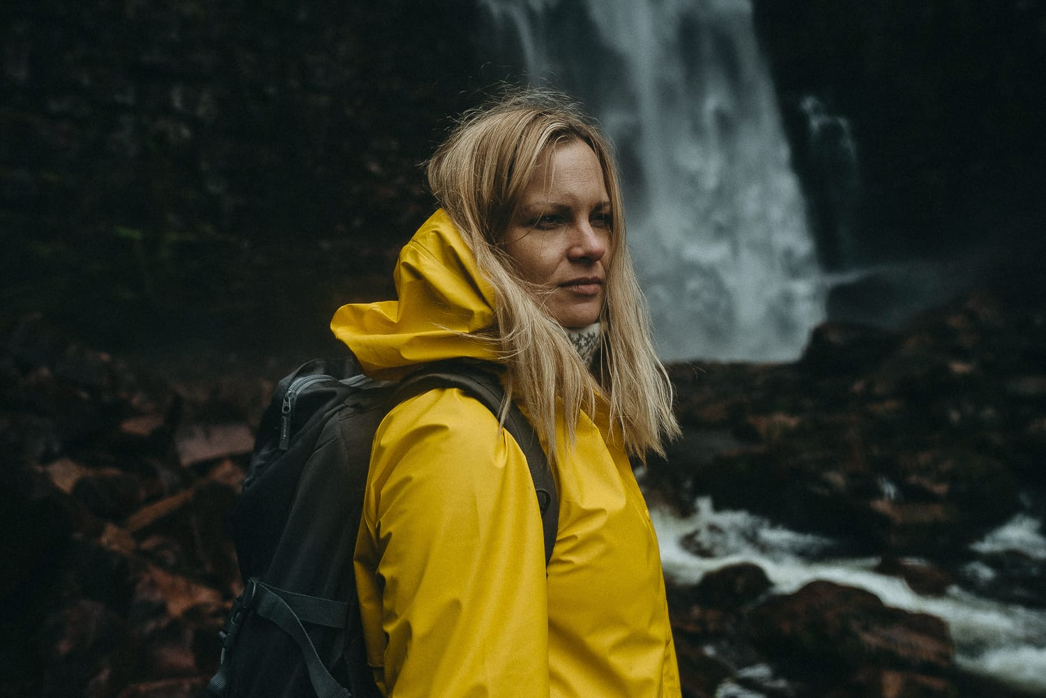 Woman in yellow raincoat by waterfall