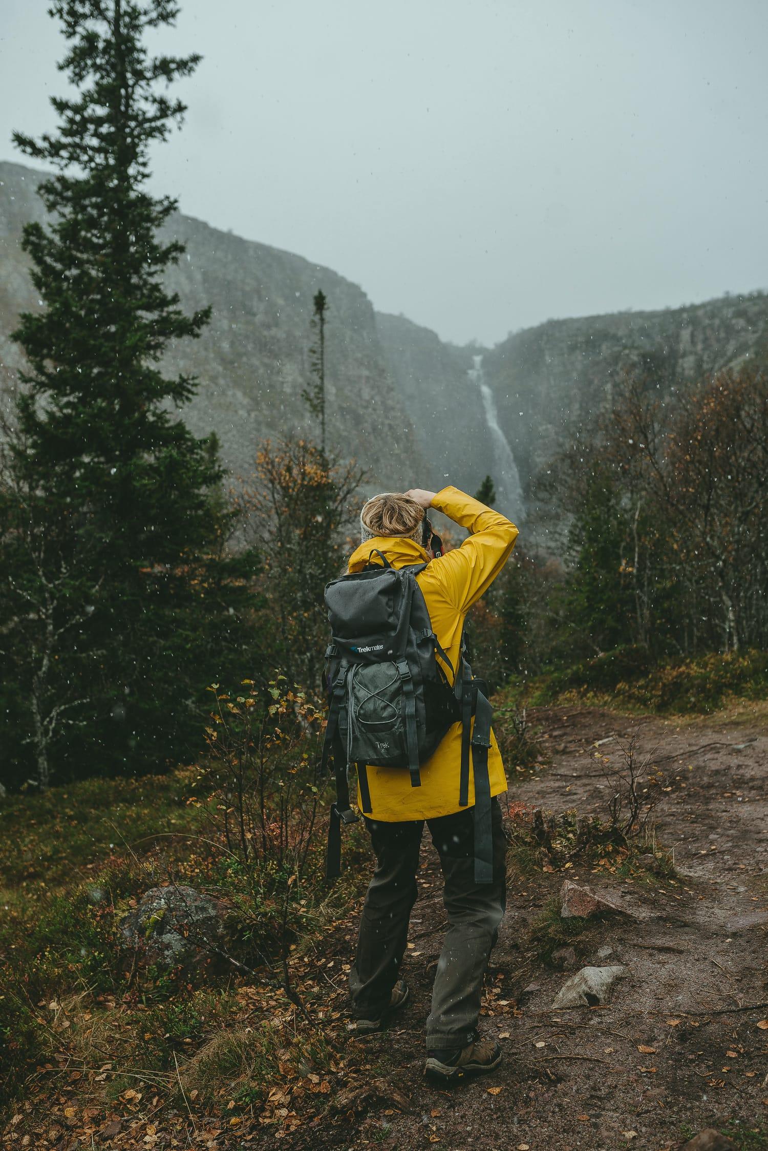 female taking a photo of Njupeskär as it snows