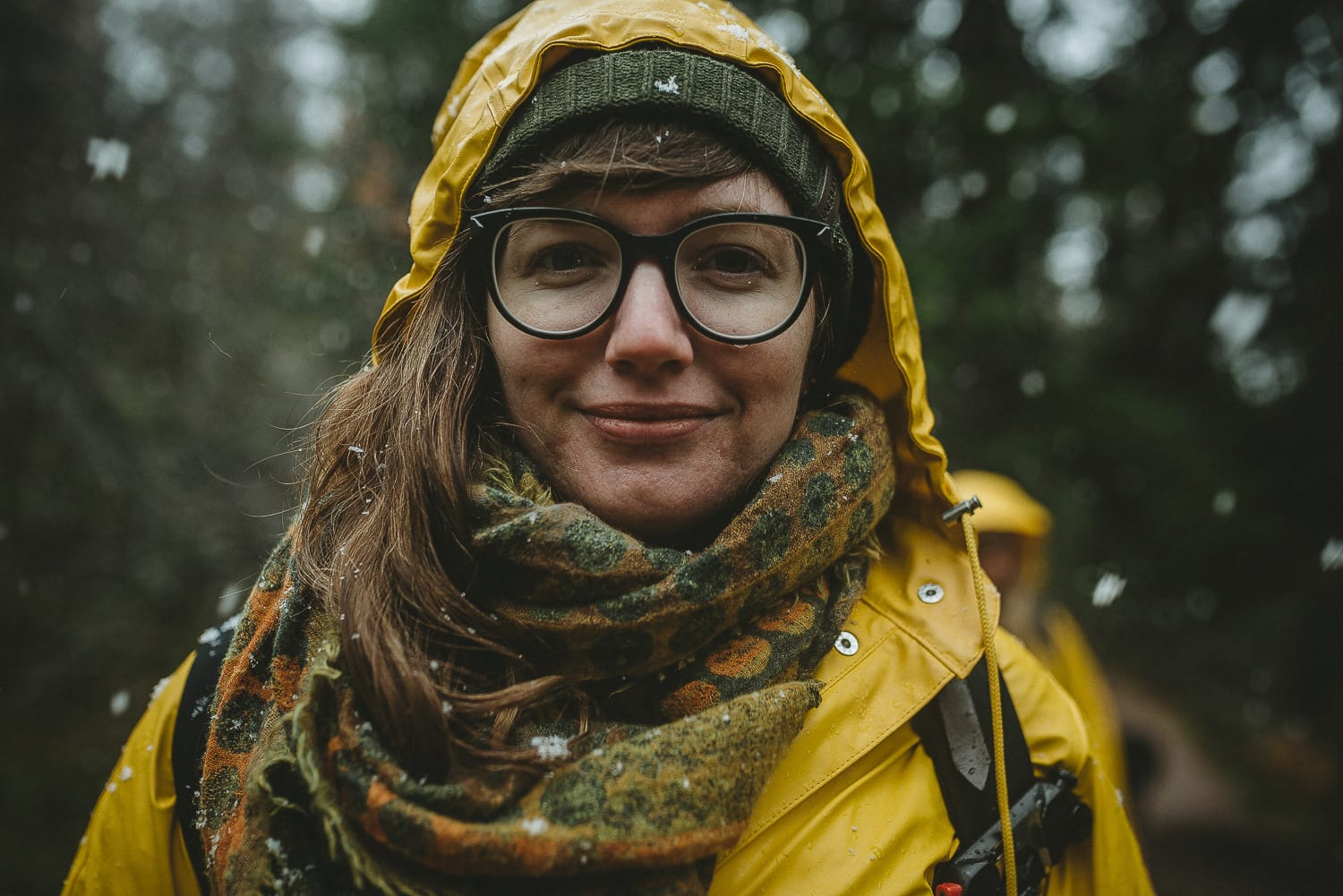 portrait of a female wearing a raincoat as it snows