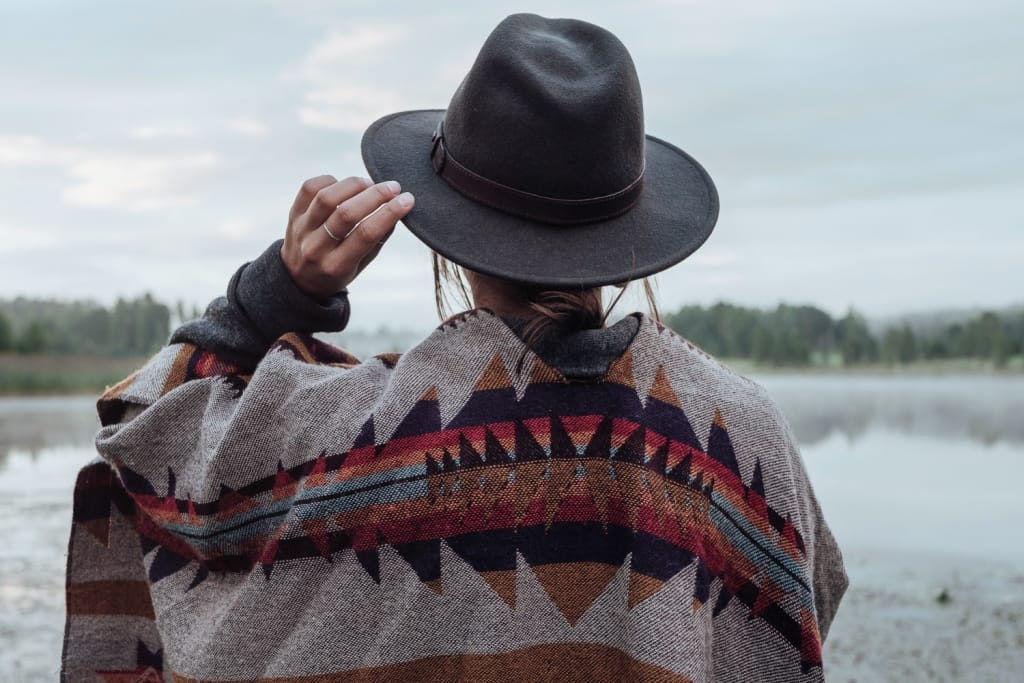 woman in poncho holding her hat