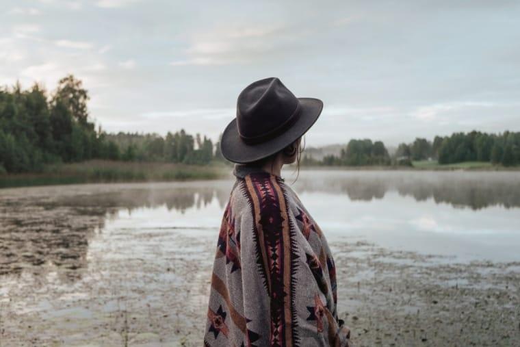 woman standing by a lake