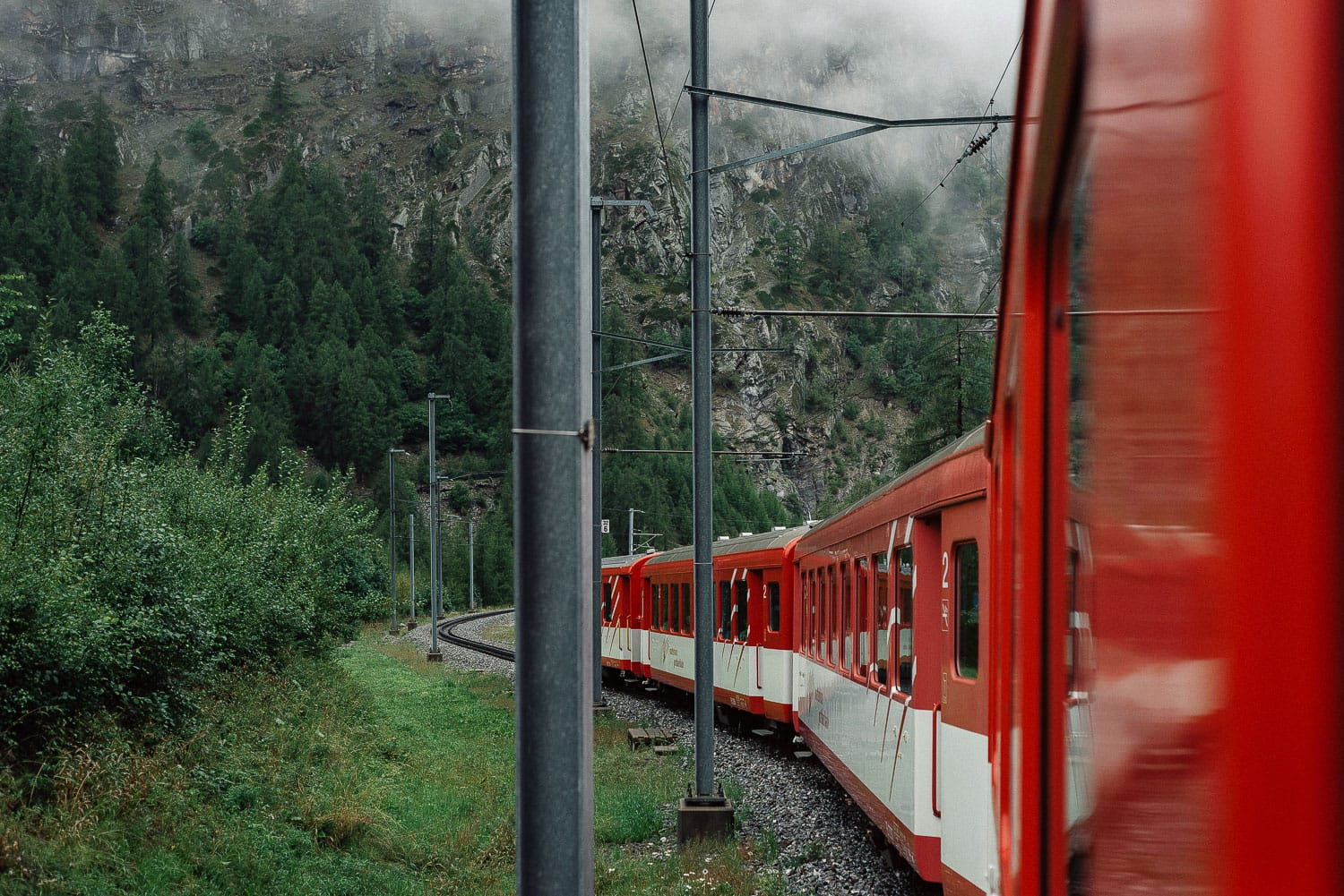 Red train passing through the Swiss mountains