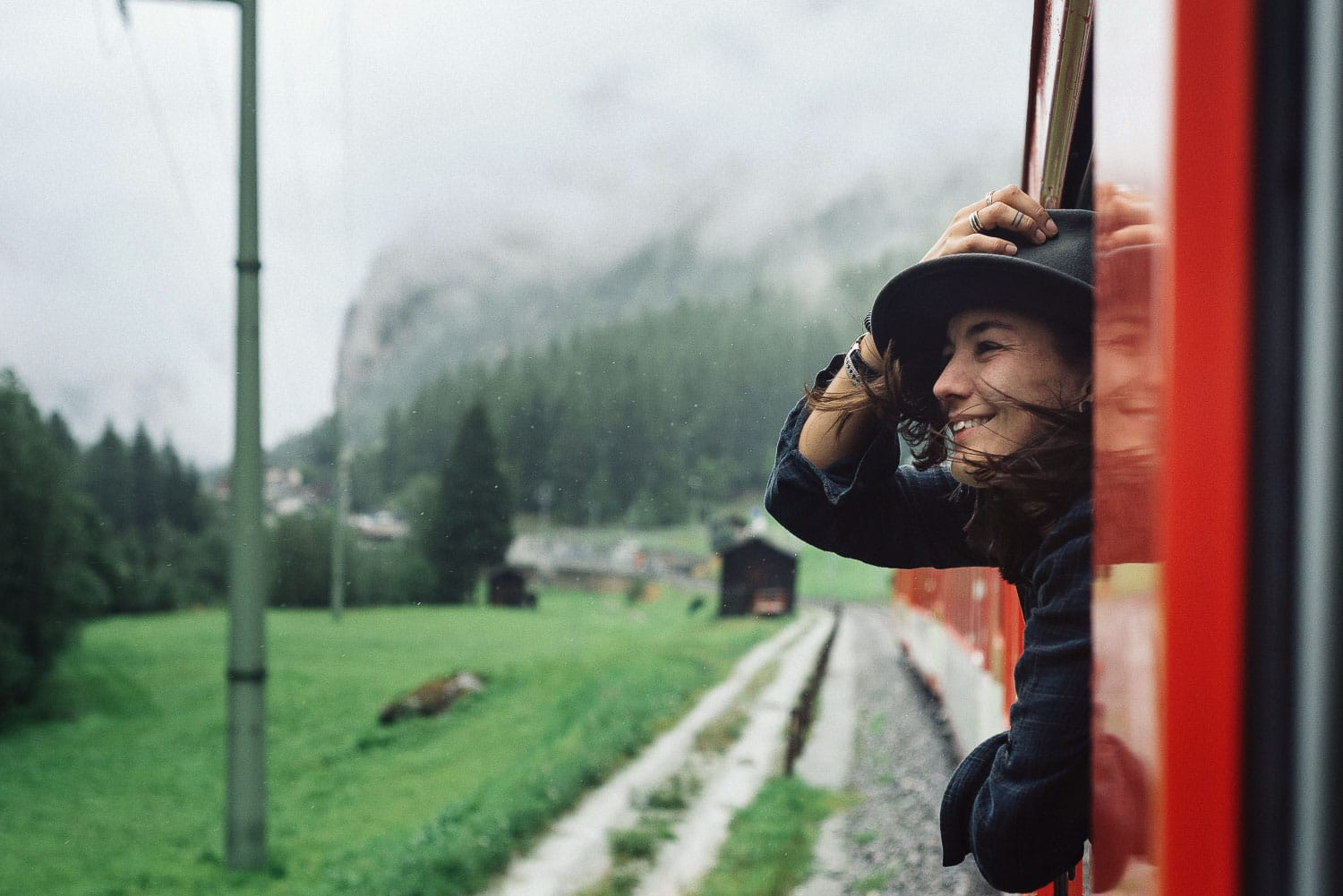 Woman with hat sticking her head out the train window in Switzerland