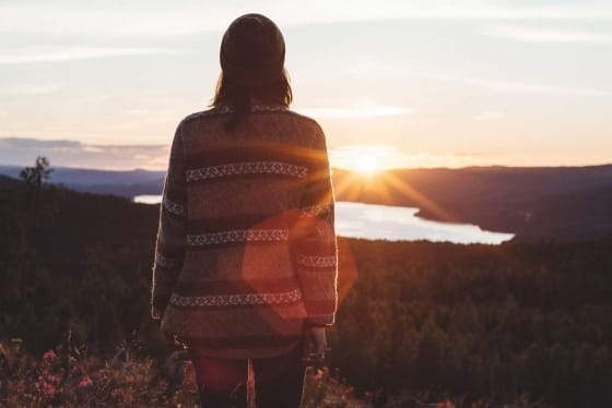 woman in chunky knits watching a sunset