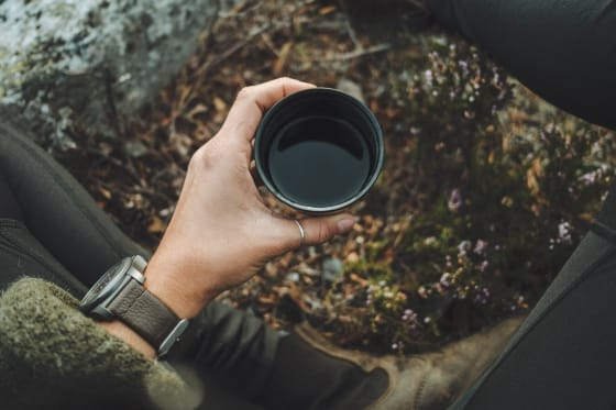 a hand holding a cup of coffee outside