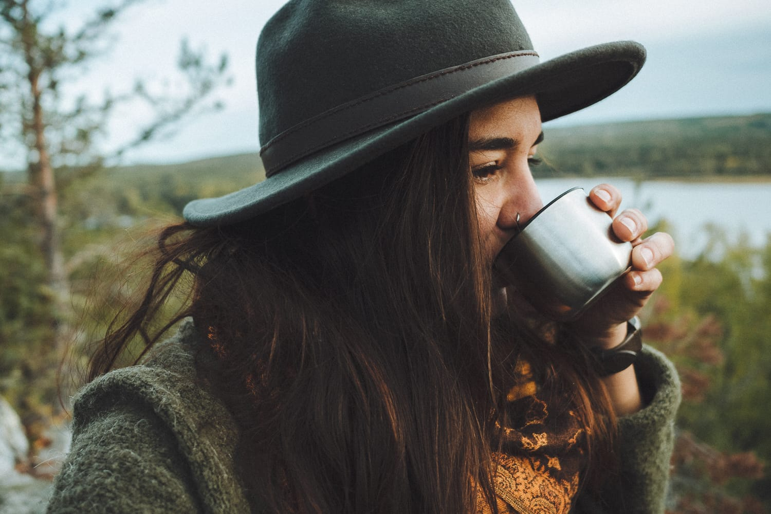 woman wearing a hat drinking coffee in the forest