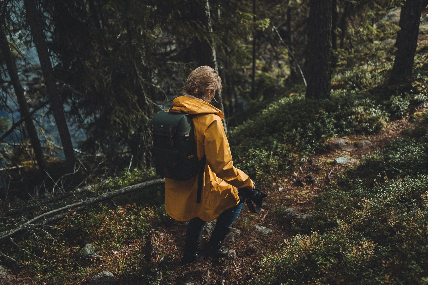 woman walking in a forest holding a camera