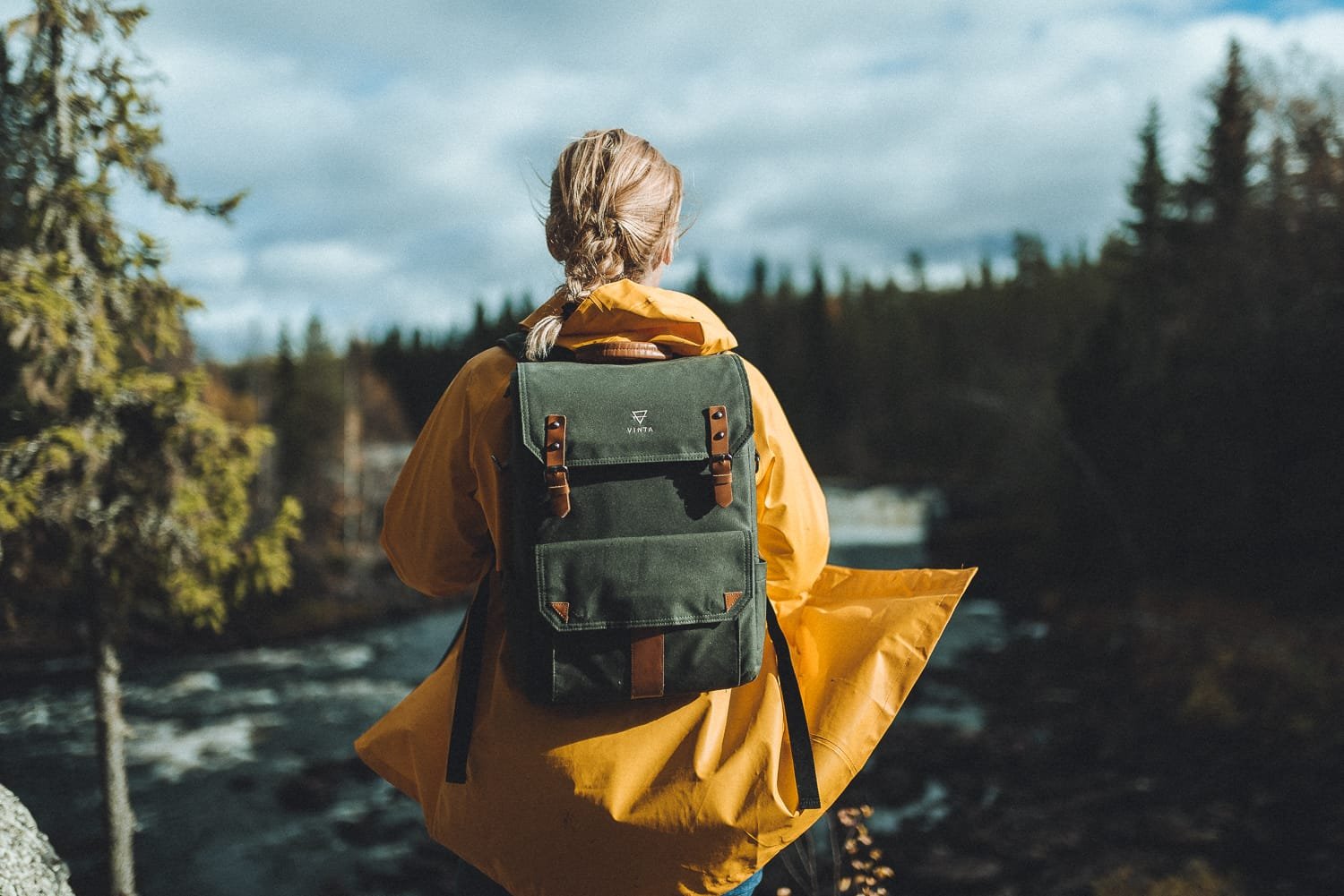 woman with green backpack overlooking a river