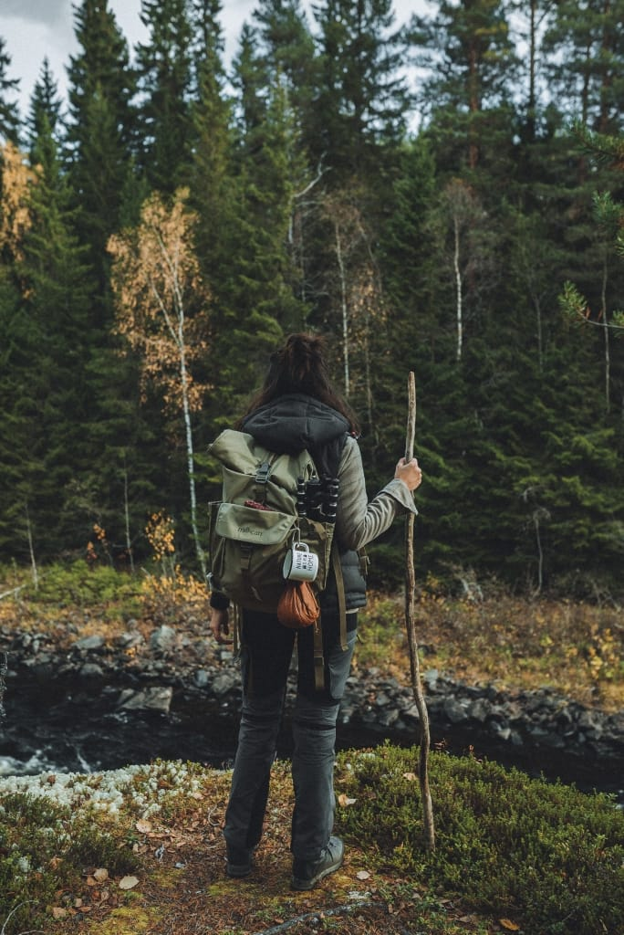 woman with backpack hiking staff