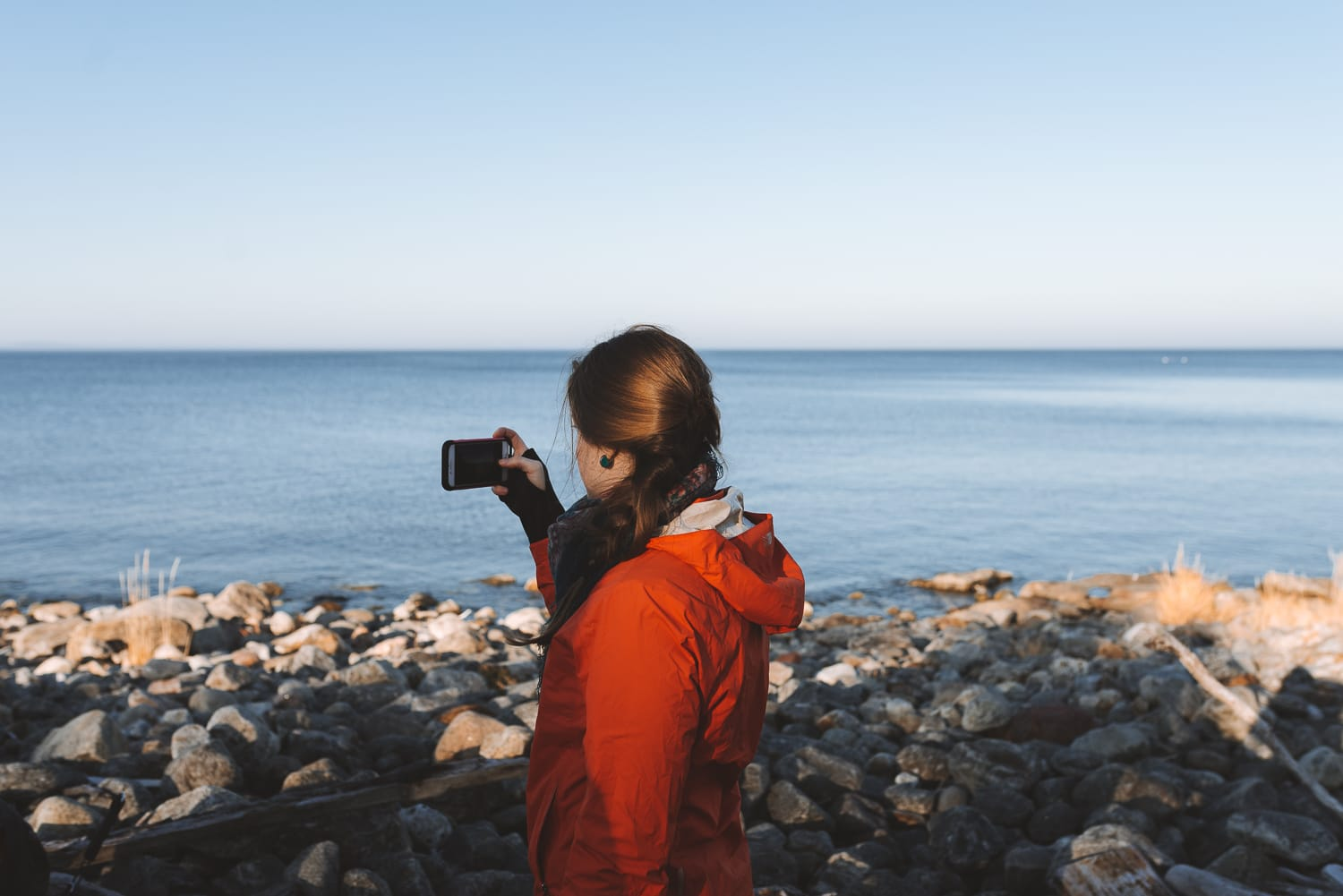 woman taking a photo of sea