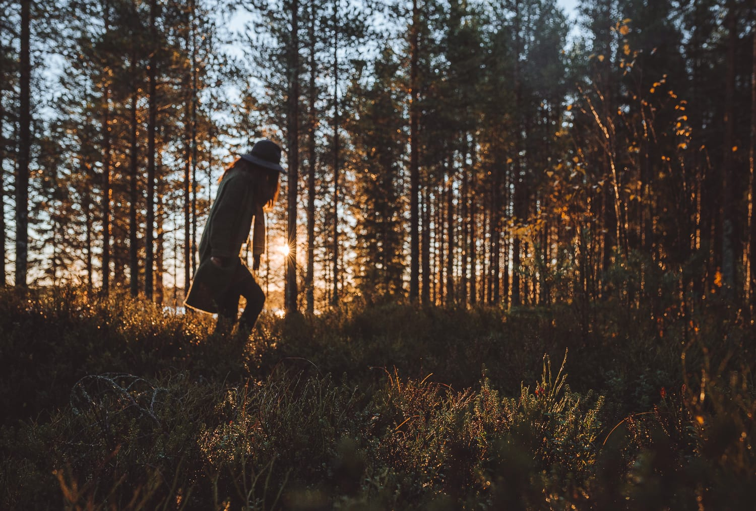 woman walking through a forest during sunrise