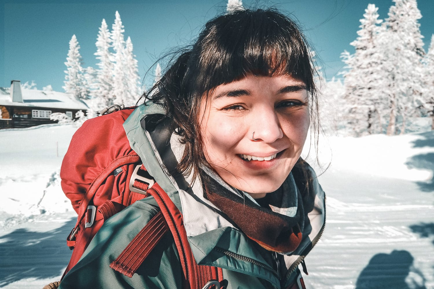 Woman with backpack smiling in the winter sun