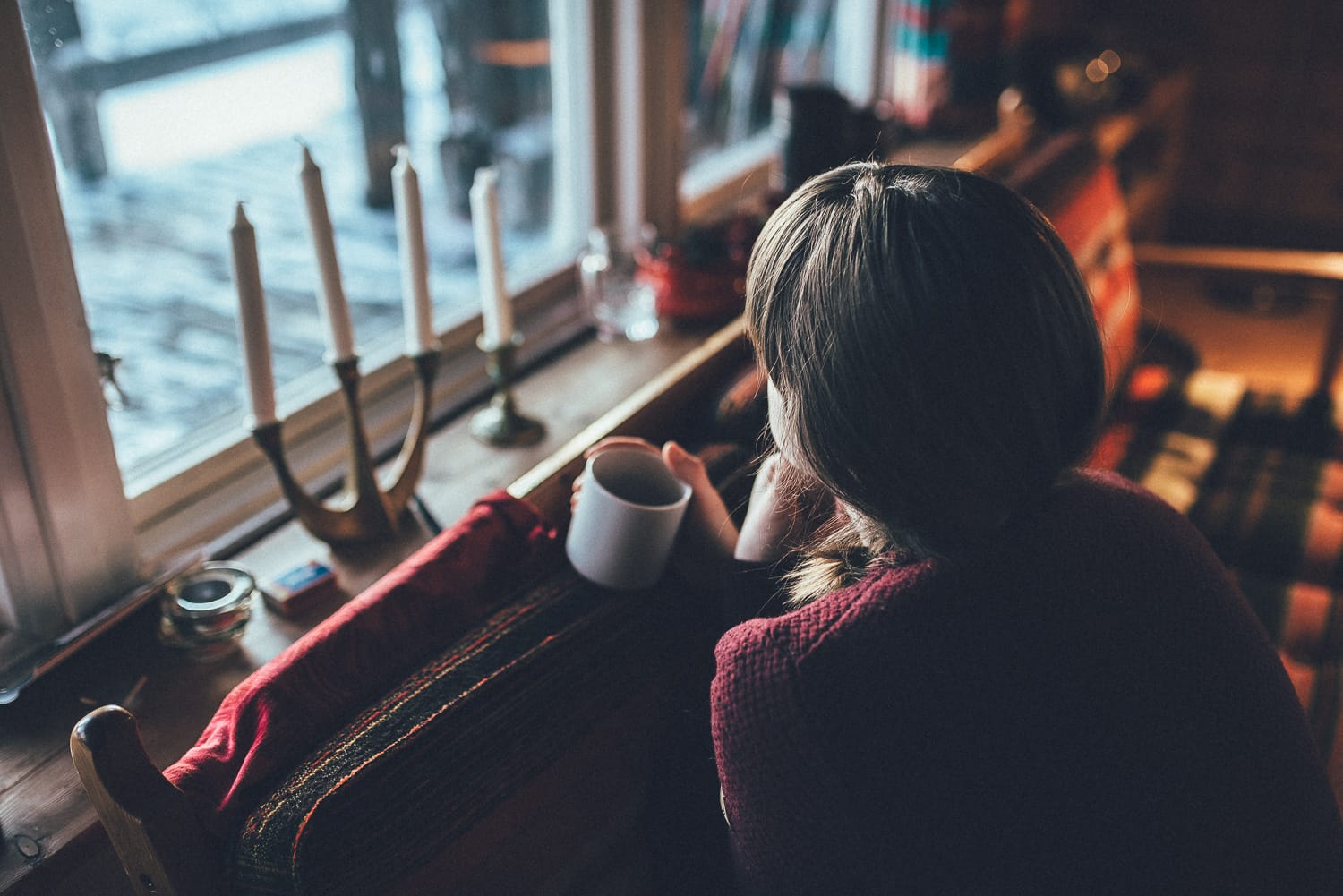 woman enjoying coffee by a cabin window