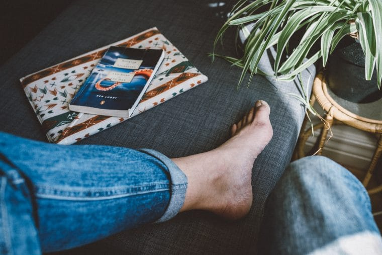 bare feet and a book on a sofa