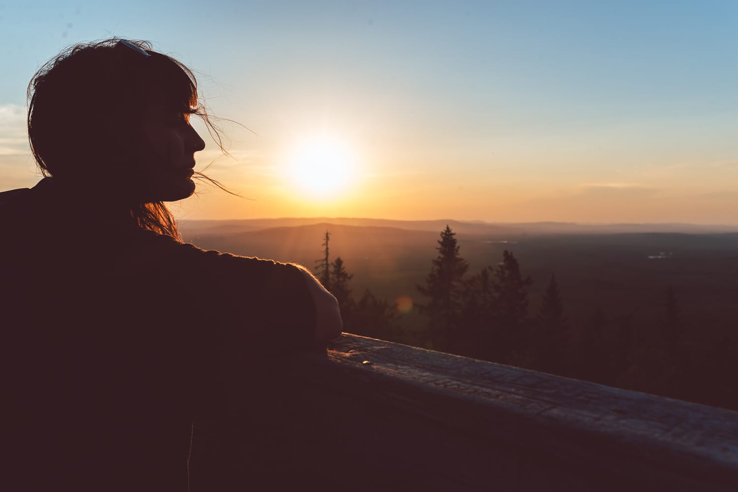 woman enjoying sunset from a watchtower