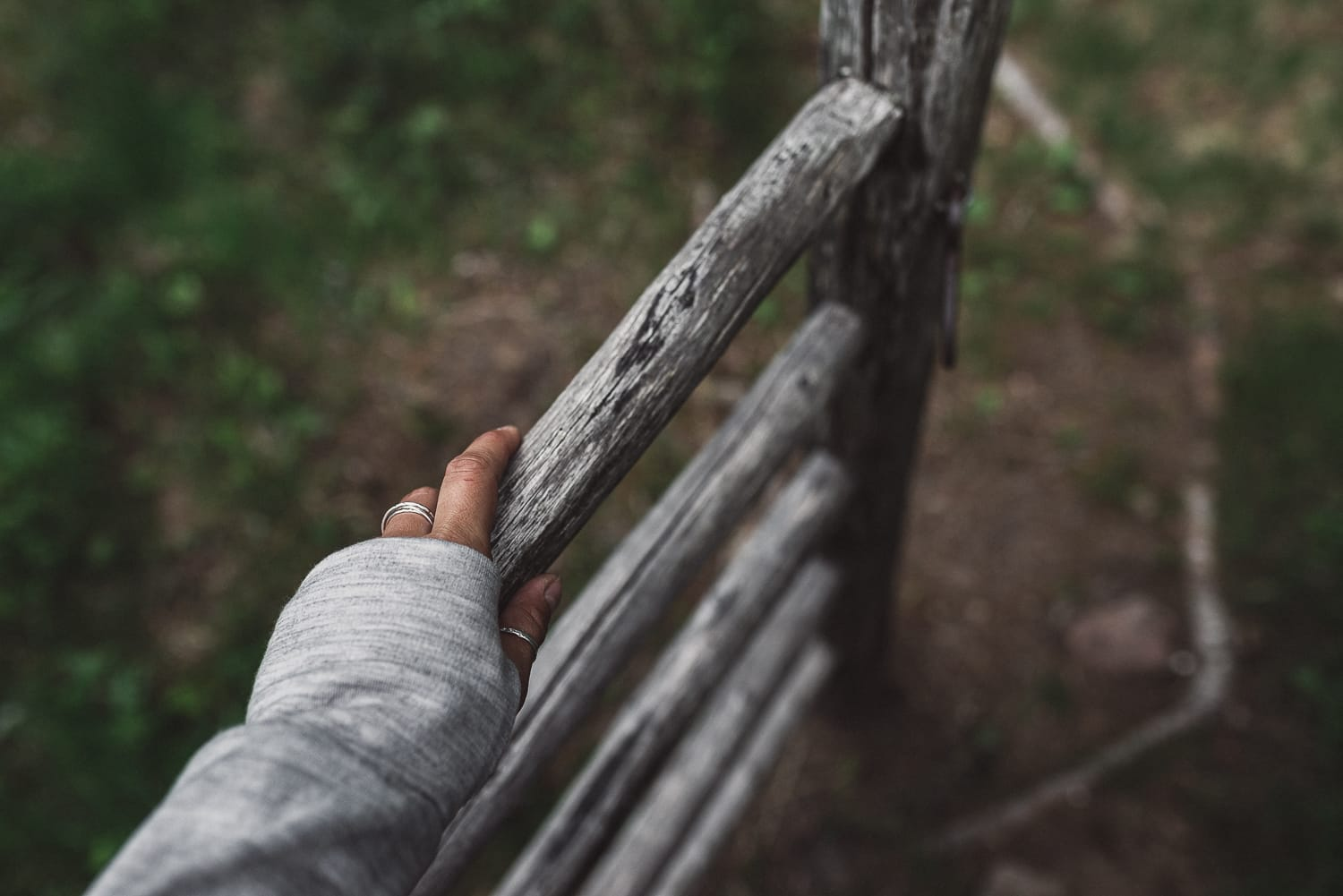 hand opening an old wooden gate