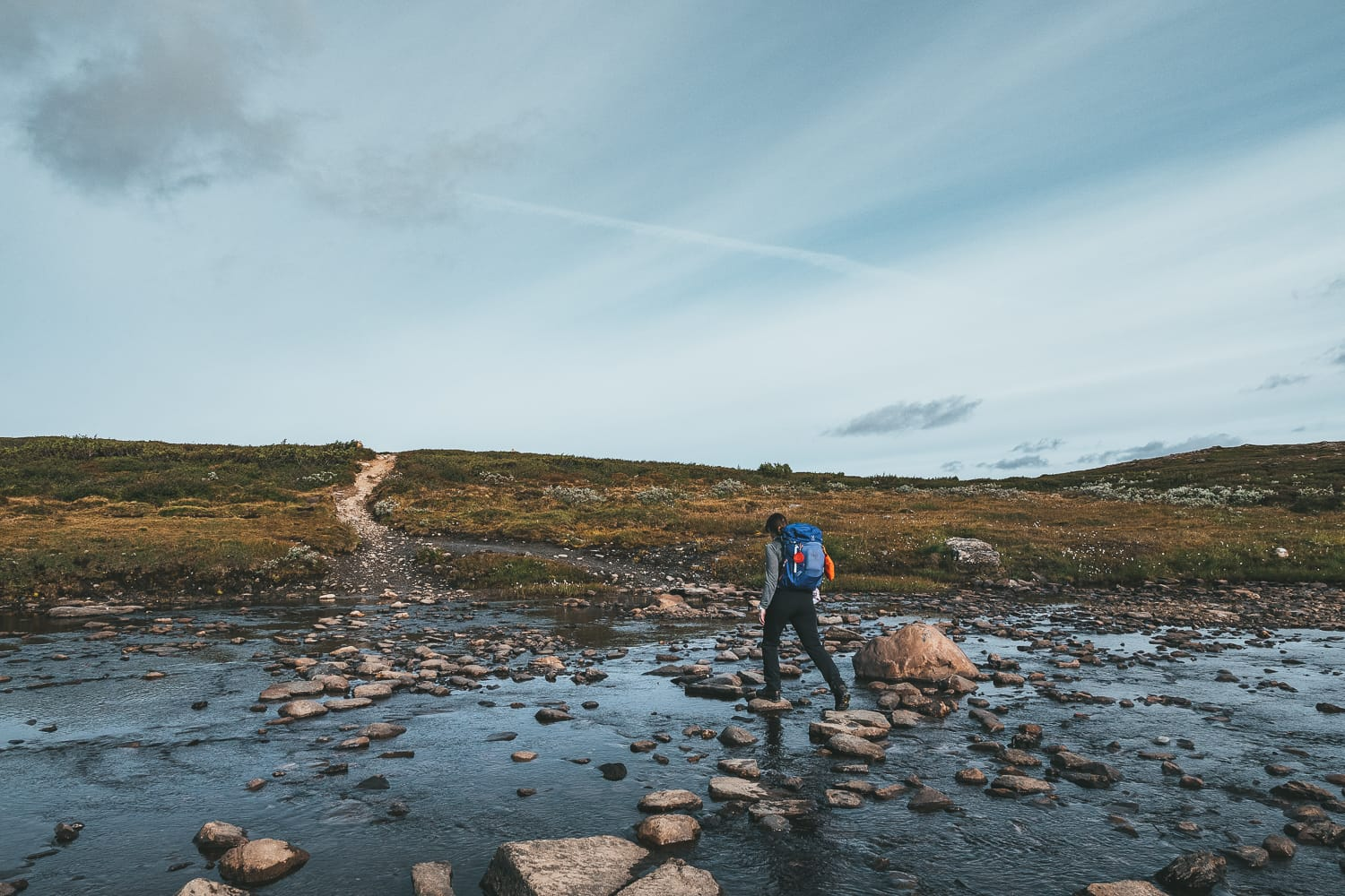 hiker crossing water in Ljungdalen
