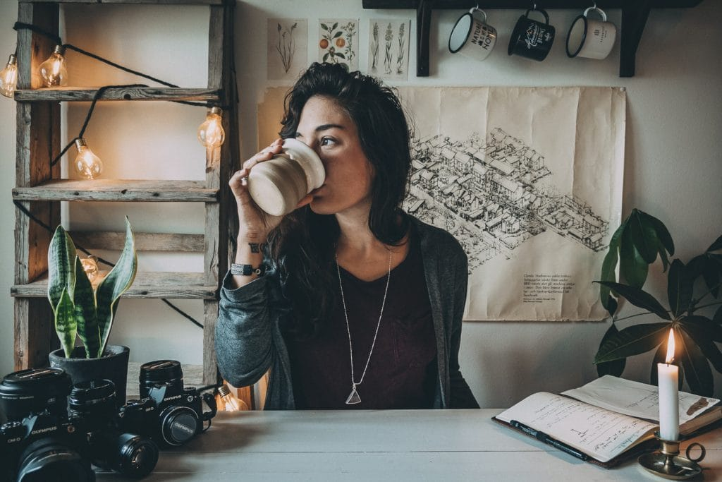 woman drinking coffee by her desk