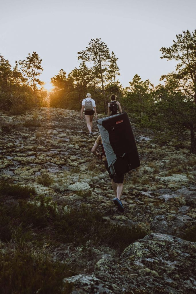 climbers with crash pads in the sunset