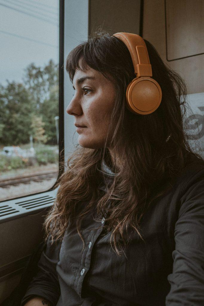 kvinna på tåg med hörlurar