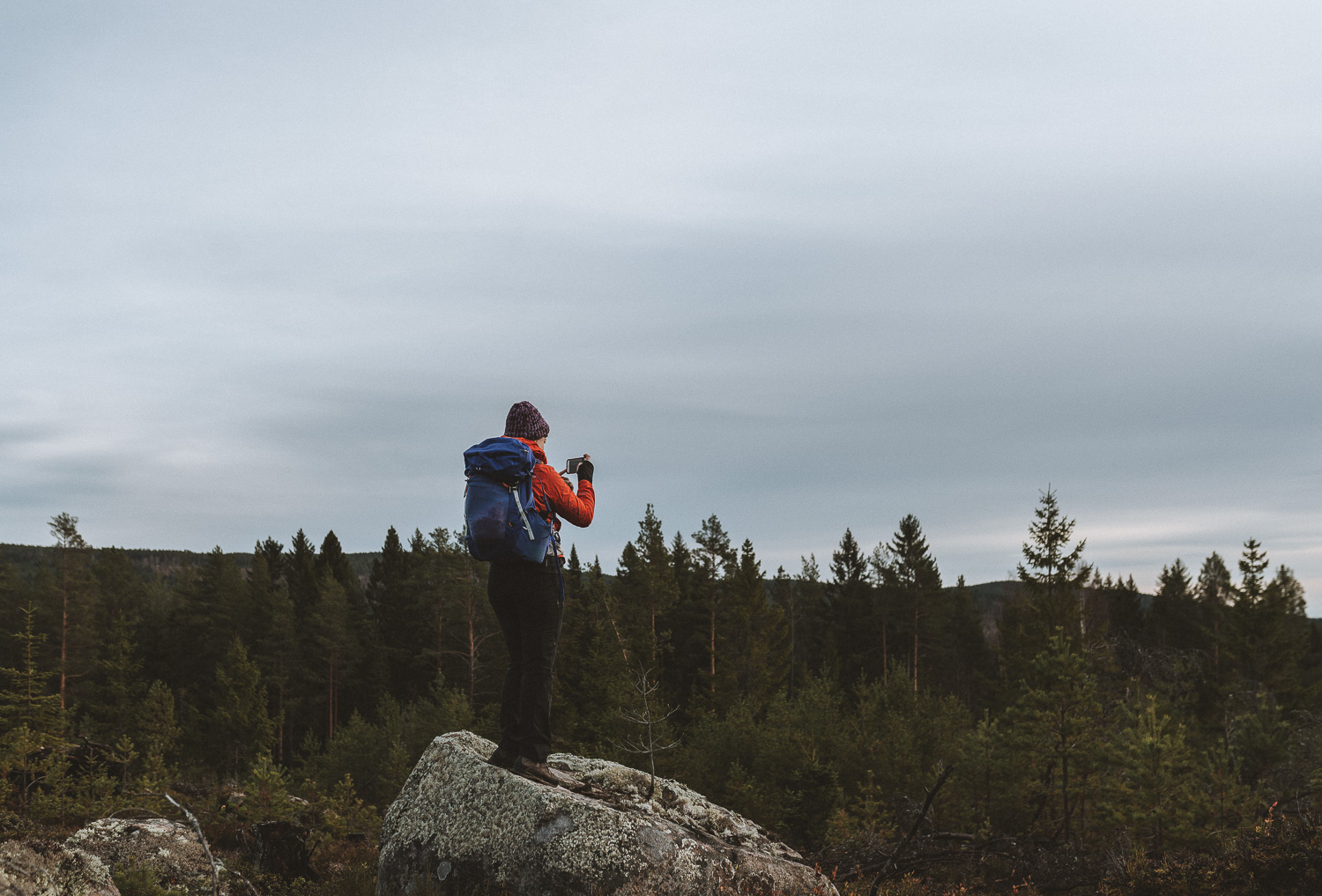 woman on top of a rock taking a photo